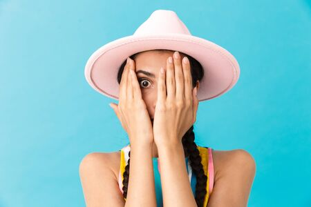 Image closeup of scared caucasian woman wearing hat covering her face and looking at camera isolated over blue wall Zdjęcie Seryjne