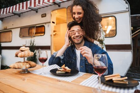 Portrait of brunette smiling woman with curly long hair covering her boyfriends eyes at dinner near trailer outdoors Stock Photo