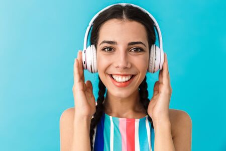 Image closeup of brunette pleased woman smiling while using headphones isolated over blue wall