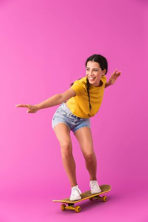 Image of young happy woman wearing casual clothes smiling and riding skateboard isolated over pink wall