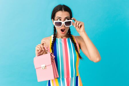 Image of brunette shocked woman wearing sunglasses looking aside while holding pink bag isolated over blue wall Фото со стока