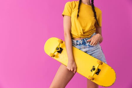 Cropped image of young caucasian woman standing and holding skateboard isolated over pink wall