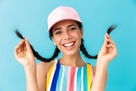 Image of alluring brunette girl wearing summer dress and cap touching her braids isolated over blue background