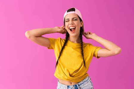 Photo of brunette joyful woman wearing cap backwards smiling and winking at camera isolated over pink wall