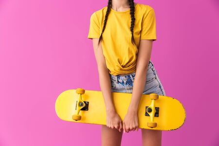 Cropped image of skinny caucasian woman standing and holding skateboard isolated over pink wall