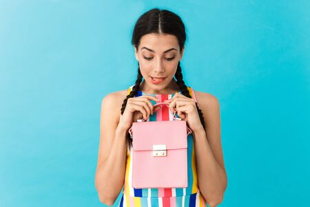 Image of puzzled caucasian woman with pigtails biting her lip while holding and looking at pink bag isolated over blue wall