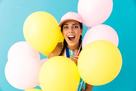 Image of happy surprised woman wearing cap looking at camera while holding air balloons isolated over blue wall