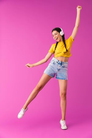 Full length of a cheerful young brunette girl standing isolated over pink background, listening to music with headphones, dancing Фото со стока