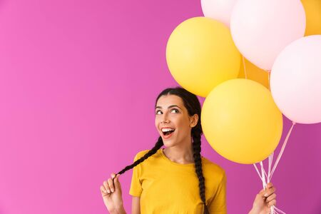 Lovely young brunette girl holding bunch of air balloons while standing isolated over pink background, celebrating