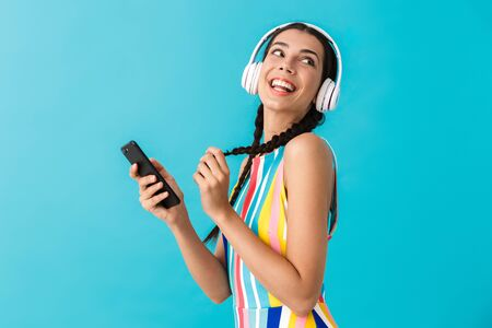 Image of nice beautiful woman with pigtails looking aside while using headphones and cellphone isolated over blue wall