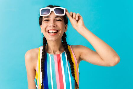 Image of brunette funny woman wearing sunglasses looking at camera and laughing isolated over blue wall Фото со стока