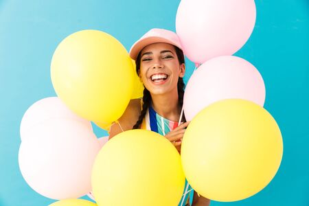 Image of happy smiling woman wearing cap looking at camera while holding air balloons isolated over blue wall