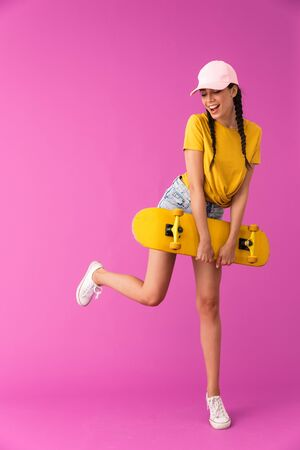 Full length image of beautiful caucasian woman wearing cap smiling and holding skateboard isolated over pink wall Фото со стока
