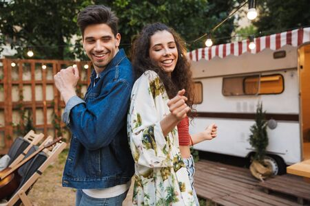 Portrait of funny couple man and woman smiling while dancing together near house on wheels outdoors Stock fotó