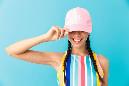 Image of stylish brunette girl wearing summer dress and cap smiling at camera isolated over blue background