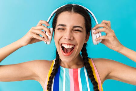 Image closeup of brunette nice woman with open mouth smiling while using headphones isolated over blue wall