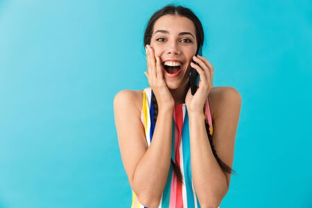 Image of amazed beautiful woman talking on cellphone and expressing surprise isolated over blue wall
