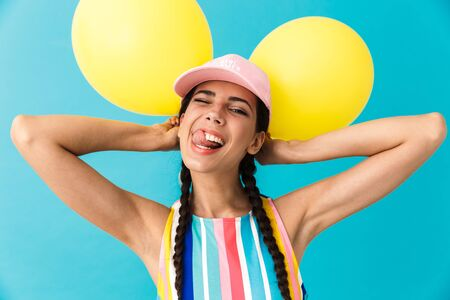 Image of young joyful woman wearing cap winking while holding two air balloons isolated over blue wall