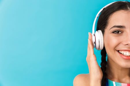 Cropped image of brunette happy woman smiling while using headphones isolated over blue wall