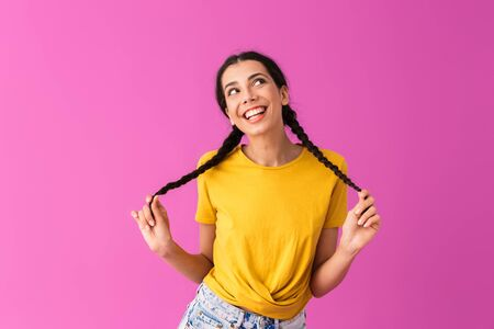Photo of young joyful woman wearing casual t-shirt smiling and touching her pigtails isolated over pink wall Stock fotó