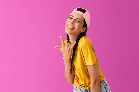 Photo of beautiful joyful woman wearing cap backwards smiling and showing rock sign isolated over pink wall