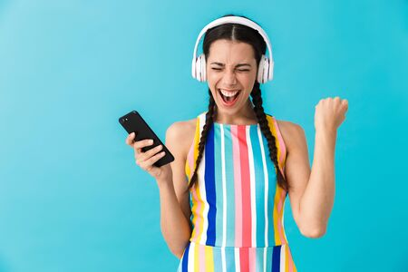 Image of brunette delighted woman using headphones and cellphone isolated over blue wall 写真素材