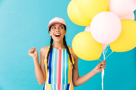 Image of cute joyful woman wearing cap looking aside at copyspace while holding air balloons isolated over blue wall