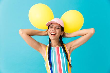 Image of young joyful woman wearing cap laughing while holding two air balloons isolated over blue wall