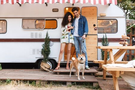 Portrait of nice couple man and woman smiling while standing with red dog near house on wheels outdoors