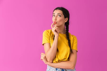 Image of pretty thoughtful woman looking at copyspace and touching her lips isolated over pink wall