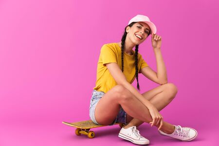 Image of young happy woman wearing casual clothes smiling and sitting on skateboard isolated over pink wall