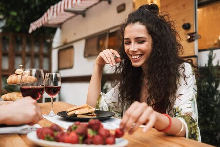 Portrait of cute couple man and woman drinking red wine while eating strawberry together at wooden table outdoors