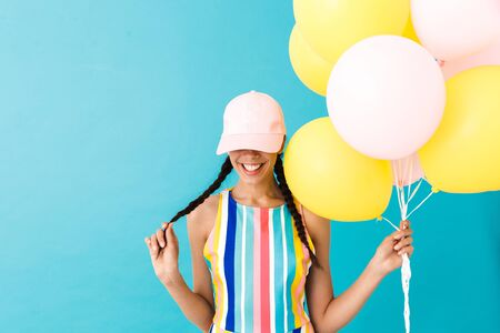 Image of cute smiling woman wearing cap looking downward at copyspace while holding air balloons isolated over blue wall