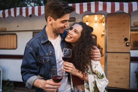 Portrait of satisfied couple man and woman drinking red wine and hugging together while standing near trailer outdoors