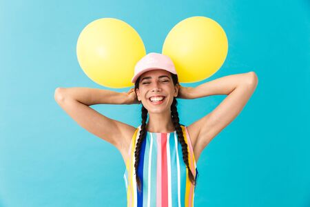 Image of nice joyful woman wearing cap laughing with eyes closed while holding two air balloons isolated over blue wall Stock Photo - 129823748