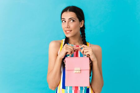 Image of thoughtful caucasian woman with pigtails holding pink bag and biting her lip isolated over blue wall Stock Photo - 129823750