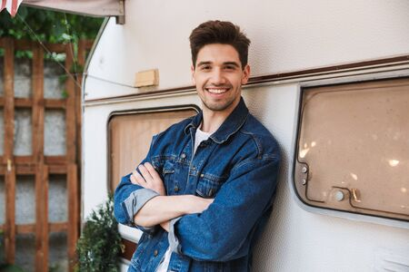 Portrait of happy handsome man wearing denim jacket smiling and looking at camera while standing near house on wheels outdoors Stock Photo
