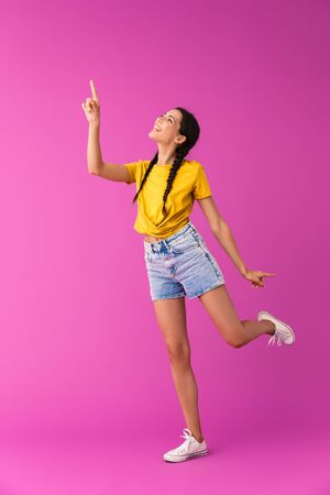 Full length of a cheerful young brunette girl standing isolated over pink background, pointing finger up Stock Photo