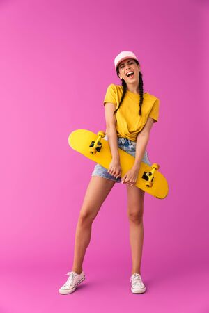 Full length image of cheerful caucasian woman wearing cap smiling and holding skateboard isolated over pink wall Stock Photo - 129823762