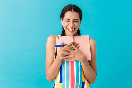 Image of delighted cute woman with eyes closed laughing while holding pen and diary book isolated over blue wall Stock Photo - 129823763