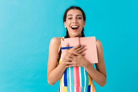 Image of delighted happy woman looking at camera while holding pen and diary book isolated over blue wall 스톡 콘텐츠