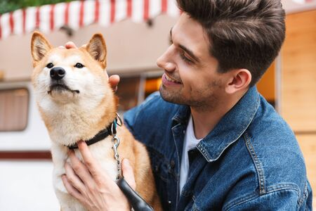 Portrait of happy smiling man wearing denim clothes petting red dog near house on wheels outdoors