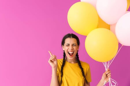 Image of amazed young woman pointing finger upward at copyspace while holding air balloons isolated over pink wall Stock Photo - 129823735