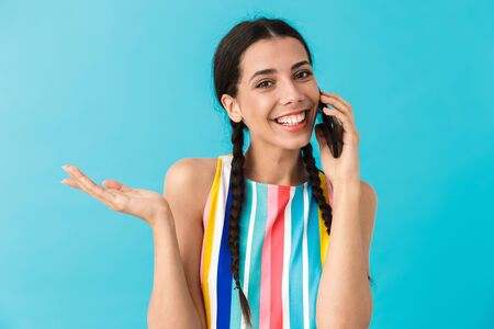 Image of smiling beautiful woman talking on cellphone and holding copyspace isolated over blue wall Stock Photo - 129823738