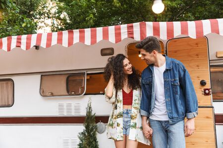 Cheerful young couple talking while standing at the campvan, holding hands