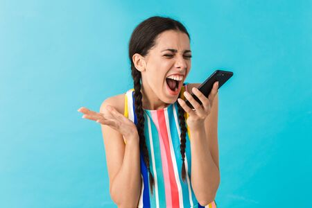Image of cute beautiful woman making video call on cellphone and expressing surprise isolated over blue wall Stock Photo - 129823707