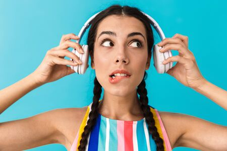 Image closeup of brunette puzzled woman looking aside and biting her lip while using headphones isolated over blue wall Фото со стока - 129823714