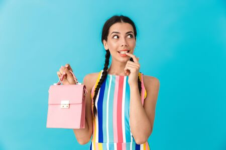 Image of thinking caucasian woman with pigtails holding pink bag and looking aside isolated over blue wall