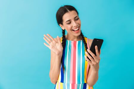 Image of pleased beautiful woman taking selfie photo on cellphone and waving hand isolated over blue wall Stock Photo - 129823719