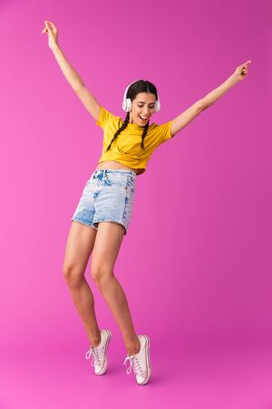 Full length of a cheerful young brunette girl standing isolated over pink background, listening to music with headphones, dancing Stock Photo - 129823721